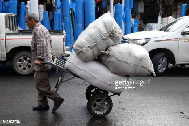 A porter carries goods on a cart in the market near the citadel on November 2 2016 in Erbil Iraq Erbil also spelt Arbil or Irbil is the capital city...