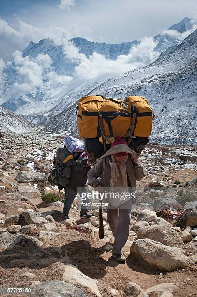 Porter carrying expedition bags mountain trail Himalayas Nepal