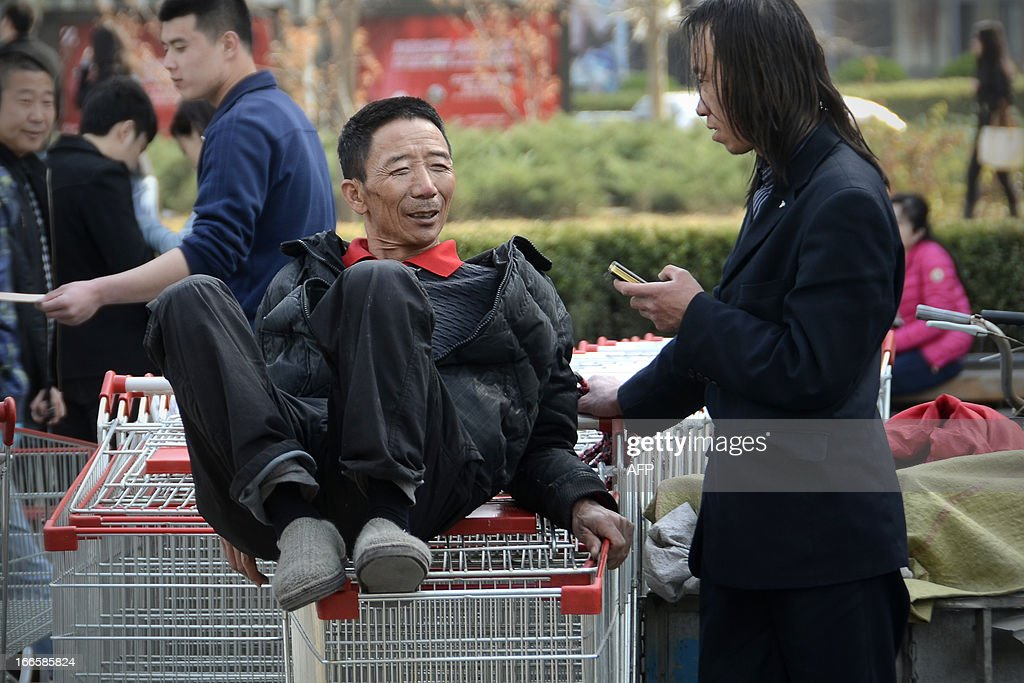 A porter (L) chats with a man as he sits on shopping cart at the entrance of a supermarket in Beijing on April 14, 2013. China's economic growth likely picked up slightly in the first quarter of this year,according to an AFP poll of analysts, but they say the rebound is fragile and key data unreliable.