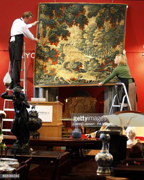 Porter David Fiddes and Antiques Department Manager Victoria Crake hang an 18th century tapestry at Lyon and Turnbull auctioneers in Edinburgh
