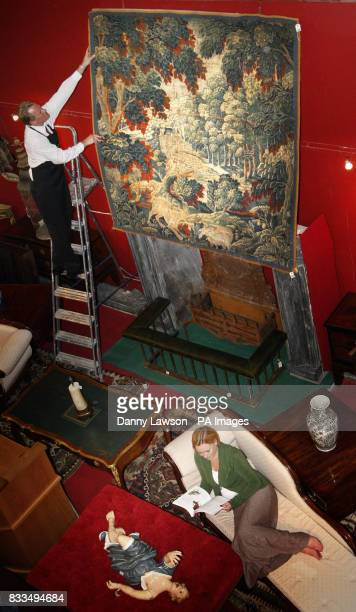 Porter David Fiddes hangs an 18th century tapestry at Lyon and Turnbull auctioneers in Edinburgh