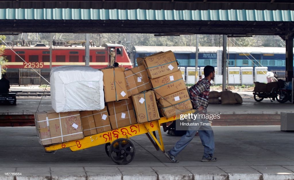 Porter push carts filled with goods at New Delhi Railway Station on February 26, 2013 in New Delhi, India. Indian Railway Minister Pawan Kumar Bansal presented his maiden Railway budget for the next fiscal year in the parliament.