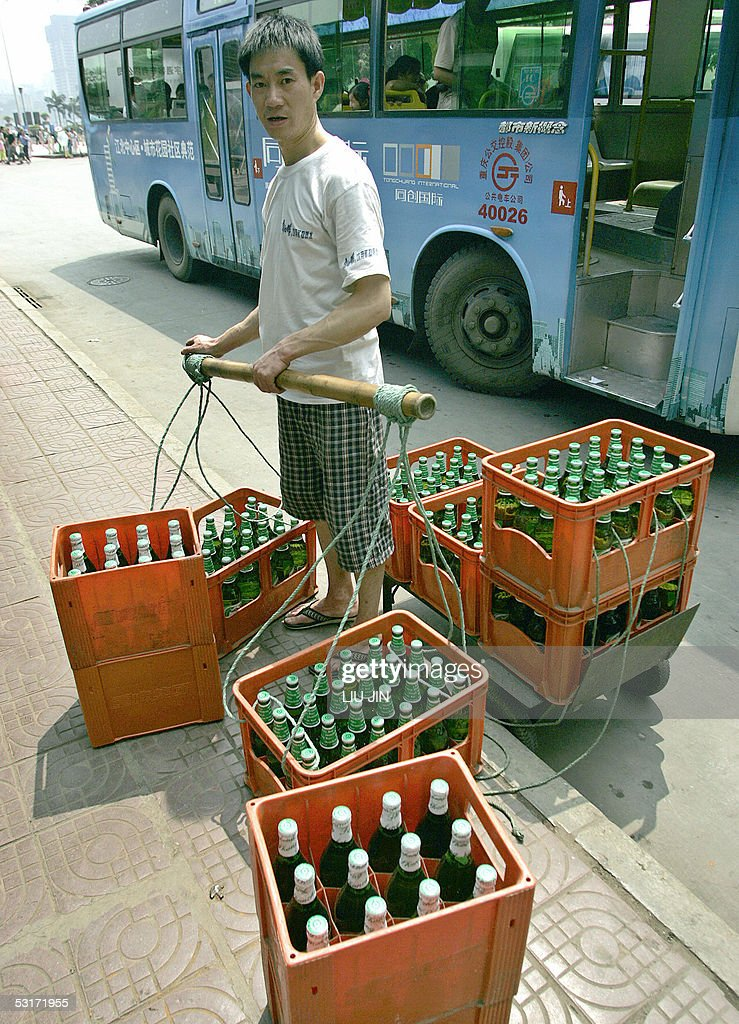 STORY 'CHINAECONOMYCHONGQING' A porter stands the crates of beers along a street in China's southwestern city of Chongqing 01 June 2005 Chongqing000...