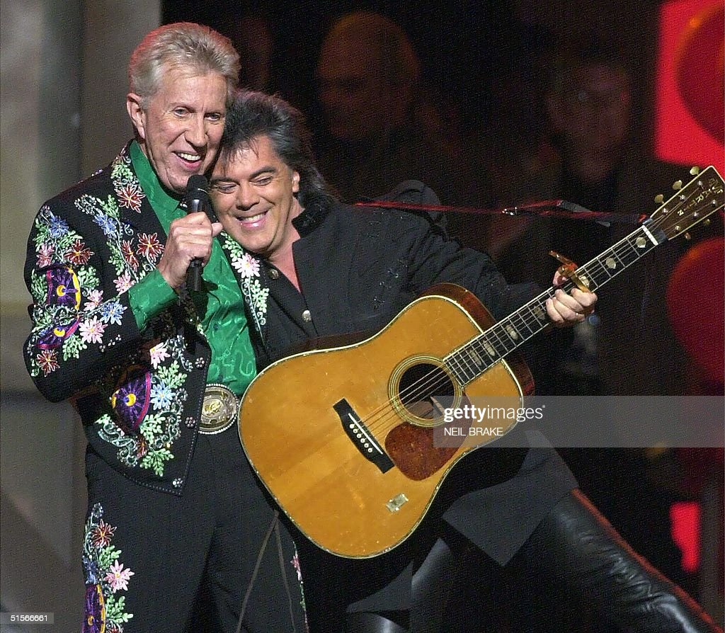 Porter Wagoner (L) gives Marty Stuart a hug on stage during the 75th Birthday celebration for country music's Grand Ole Opry 14 October, 2000, in Nashville, Tennessee. Several country music stars showed up to help celebrate the event. AFP PHOTO/Neil BRAKE