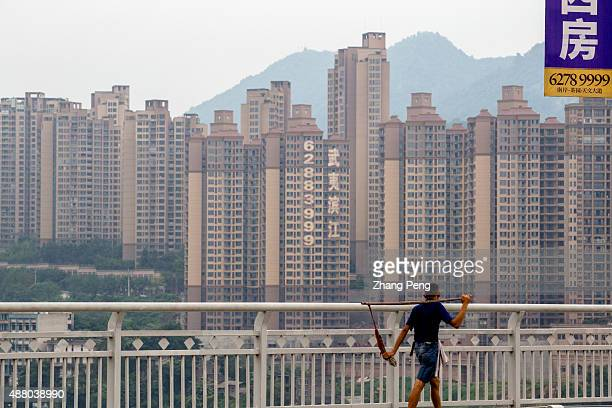 A porter walks on a bridge in the background is a large scaled new residential buildings Chinese home prices rose in August for the first time this...
