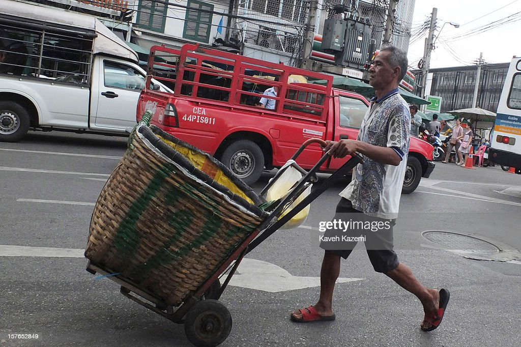 A porter with a push cart seen on a busy street on October 25, 2012 in Bangkok, Thailand.