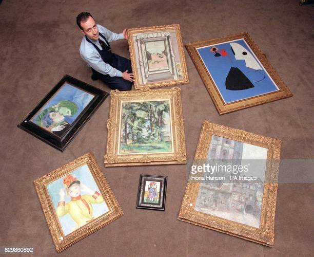 A porter with a selection of artworks from the Sotheby's London sale of Impressionist and Modern Art