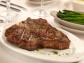 Porterhouse steak with butter and herbs and a side of asparagus with hollandaise sauce.