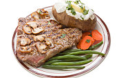 """""""A high angle close up of a plate containing a steak dinner, consisting of a porterhouse steak grilled medium rare, sauteed mushrooms, a baked potato with butter and sour cream, lightly steamed carrot"""