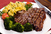 A mouth watering porterhouse steak with fresh vegetables and pasta