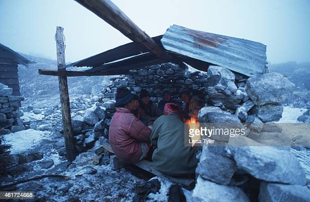 MT KANCHENDZONGA SIKKIM INDIA Porters warming themselves beside a fire at a camp on the way to Mount Kanchendzonga At 8585 meters Kanchendzonga is...