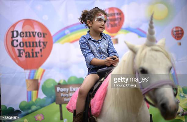 Portia Wiison of Highlands Ranch is riding the Unicorn Pony at Denver County Fair in National Western Complex Denver Colorado August 02 2014