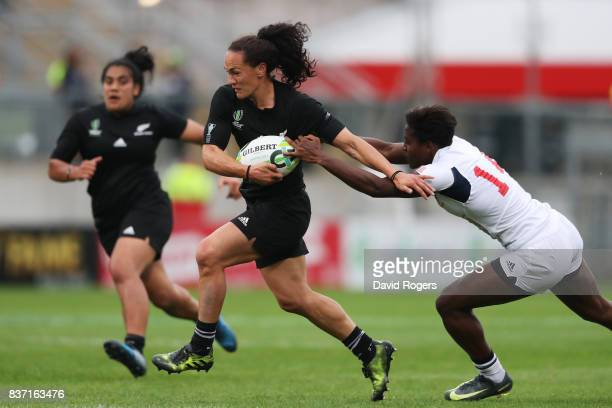 Portia Woodman of New Zealand hands off Naya Tapper of the United States enroute to scoring her team's second try during the Women's Rugby World Cup...