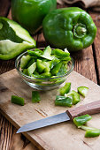Portion of green Peppers (sliced; selective focus) on wooden background