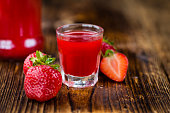 Homemade Strawberry liqueur on an wooden table as detailed close-up shot; selective focus