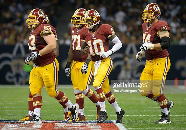A portion of the Redskins offense makes their way onto the field L to R center Will Montgomery tackle Trent Williams quarterback Robert Griffin III...
