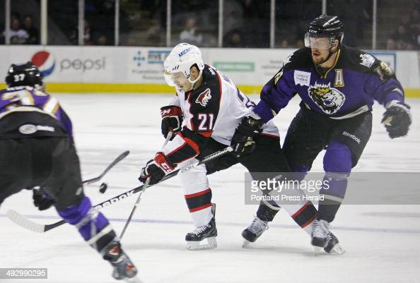 Portland Andy Miele attempts to settle the puck between Manchester Thomas Hickey and Richard Clune during second period action at Pirates vs...