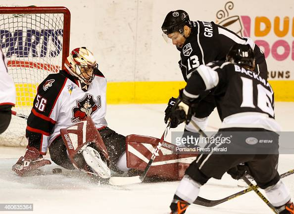 Portland Pirates goalie Mike McKenna sits on the puck while under heavy preasure by Manchester Monarchs Josh Gratton at the Cross Insurance Arena on...