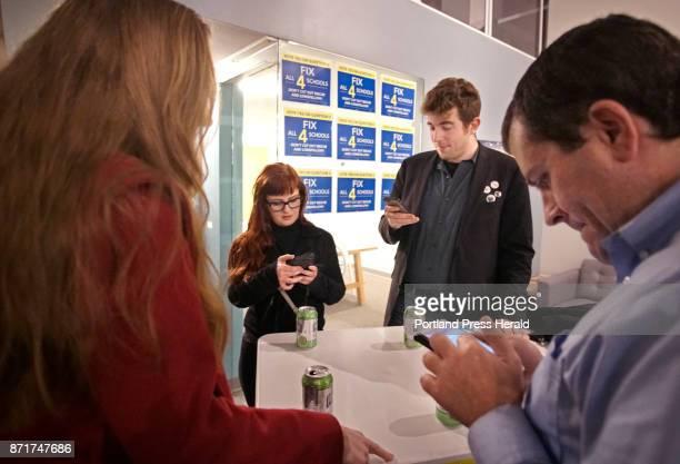 Portland School Board memeber Holly Seeliger left Matt Tanzi center and Sen Ben Chipman right check election results on their phones at Think Tank in...