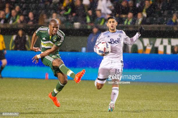 Portland Timbers midfielder Darlington Nagbe takes a shot from outside the box marked by Vancouver Whitecaps midfielder Matias Laba during the first...