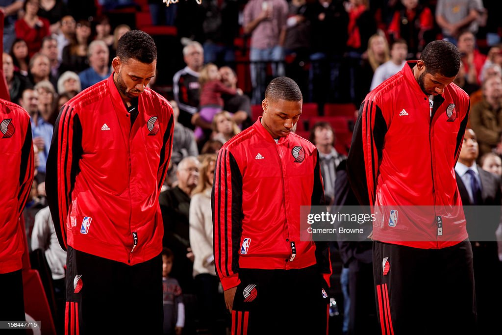 Portland Trail Blazers players, from left, Jared Jeffries #1, Damian Lillard #0 and LaMarcus Aldridge #12 listen to the National Anthem before playing against the New Orleans Hornets on December 16, 2012 at the Rose Garden Arena in Portland, Oregon.