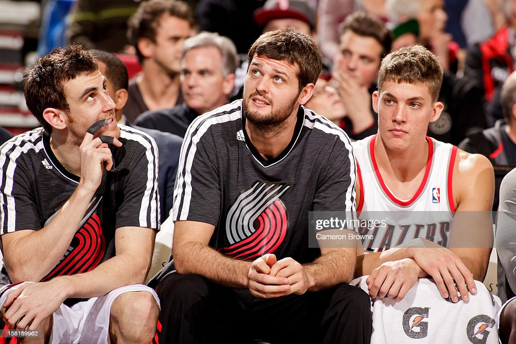 Portland Trail Blazers players, from left, <a gi-track='captionPersonalityLinkClicked' href=/galleries/search?phrase=Victor+Claver&family=editorial&specificpeople=5562510 ng-click='$event.stopPropagation()'>Victor Claver</a> #18, <a gi-track='captionPersonalityLinkClicked' href=/galleries/search?phrase=Joel+Freeland&family=editorial&specificpeople=757235 ng-click='$event.stopPropagation()'>Joel Freeland</a> #19 and <a gi-track='captionPersonalityLinkClicked' href=/galleries/search?phrase=Meyers+Leonard&family=editorial&specificpeople=6893999 ng-click='$event.stopPropagation()'>Meyers Leonard</a> #11 sit on the bench during a game against the Toronto Raptors on December 10, 2012 at the Rose Garden Arena in Portland, Oregon.