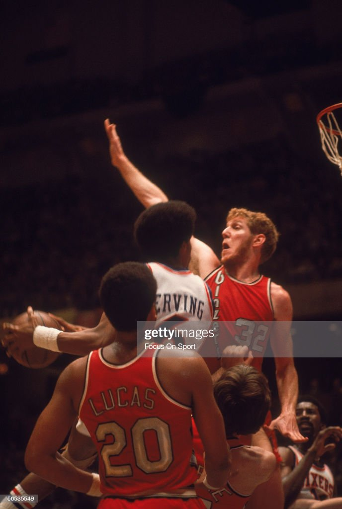 Portland Trailblazers Maurice Lucas watches as Julius Erving of the Philadelphia 76ers jumps and shoots aside Bill Walton circa May of 1977 during...