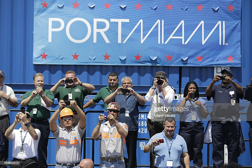 PortMiami workers take pictures as President Obama speaks during a visit to PortMiami in Miami, Florida, Friday, March 29, 2013. The president was in Miami to deliver a speech about the economy.