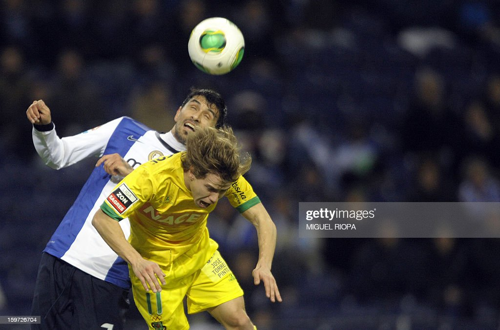 Porto's Argentinian midfielder Lucho Gonzales (L) vies with Pacos Ferreira's forward Rui Caetano during the Portuguese league football match FC Porto vs Pacos Ferreira at the Dragao stadium in Porto on January 19, 2013. AFP PHOTO/ MIGUEL RIOPA