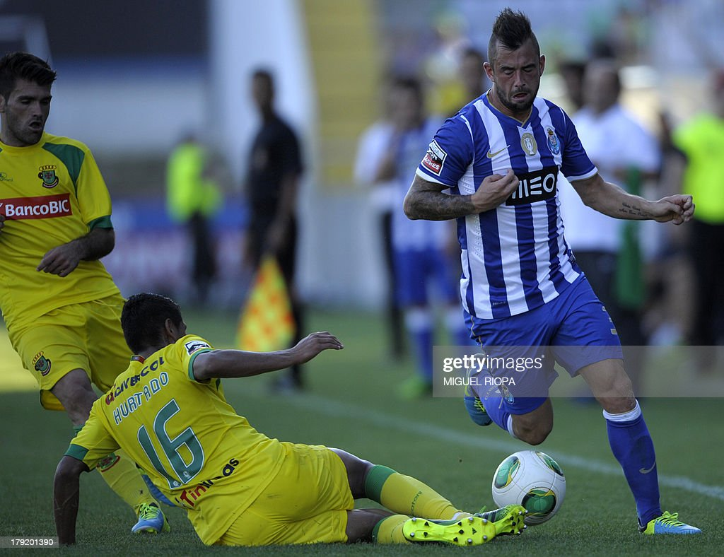 Porto's Belgian midfielder Steven Defour (R) vies with Pacos Ferreira's Peruvian forward Paolo Hurtado (C) during their Portuguese super league football match Pacos Ferreira vs FC Porto at the Machado Matos stadium in Felgueiras, on September 1, 2013.