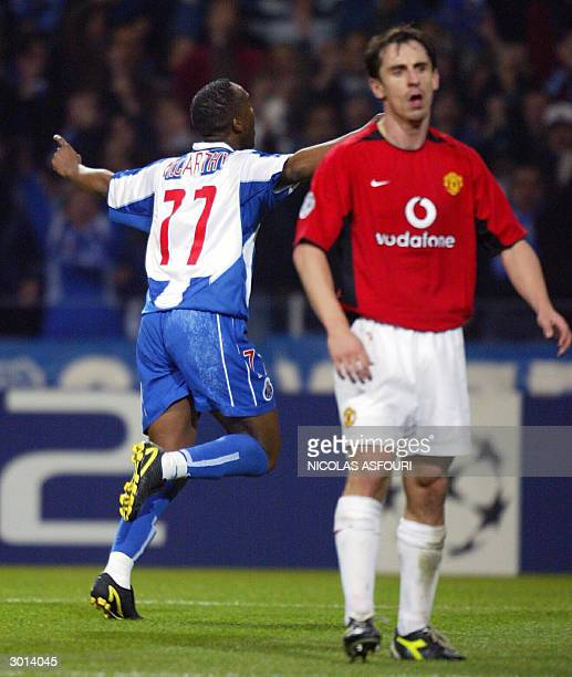 Porto's Benni McCarthy celebrates after scoring the second goal as Manchester United's Gary Neville reacts at the Dragon stadium in Porto 25 February...