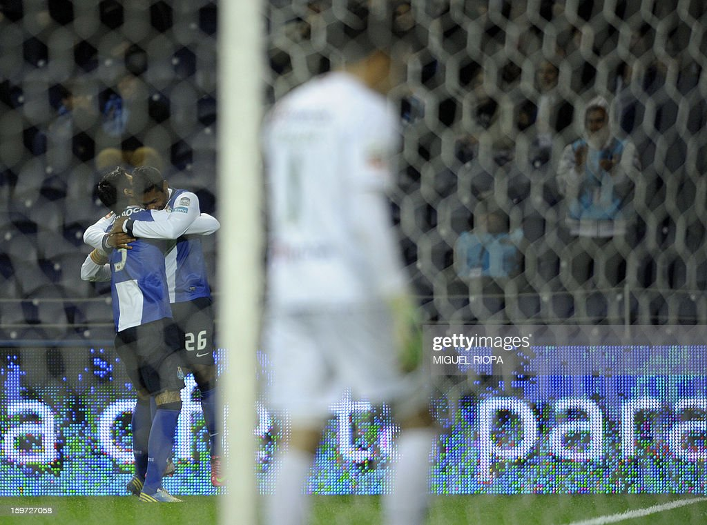Porto's Brazilian defender Alex Sandro (2ndL) is congratulated by teammate Portos Argentinian midfielder Lucho Gonzales (L) after scoring a goal during the Portuguese league football match FC Porto vs Pacos Ferreira at the Dragao stadium in Porto on January 19, 2013.