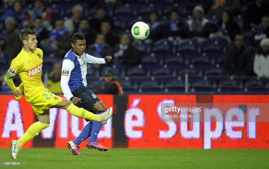 Porto's Brazilian defender Alex Sandro (R) kicks the ball next to Pacos Ferreira's defender Diogo Figueiras (L) to score a goal during the Portuguese league football match FC Porto vs Pacos Ferreira at the Dragao stadium in Porto on January 19, 2013. Porto won the match 2-0.