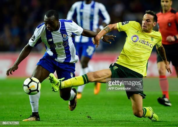 Porto's Cameroonian forward Vincent Aboubakar challenges Pacos de Ferreira's midfielder Andre Leao during the Portuguese league football match FC...