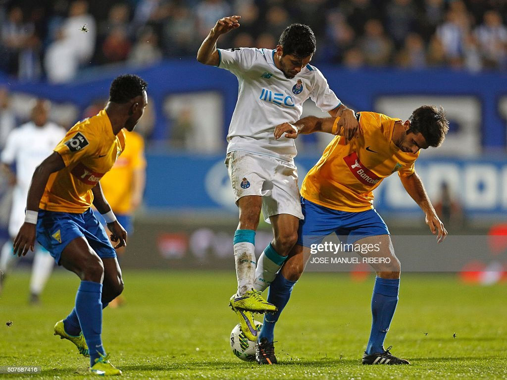 Porto's Mexican forward Jesus Corona (C) vies with Estoril's midfielder Afonso Taira (R) and Brazilian midfielder Gladstony during the Portuguese league football match GD Estoril Praia vs FC Porto at the Antonio Coimbra da Mota stadium in Estoril on January 30, 2016. AFP PHOTO/ JOSE MANUEL RIBEIRO / AFP / JOSE MANUEL RIBEIRO