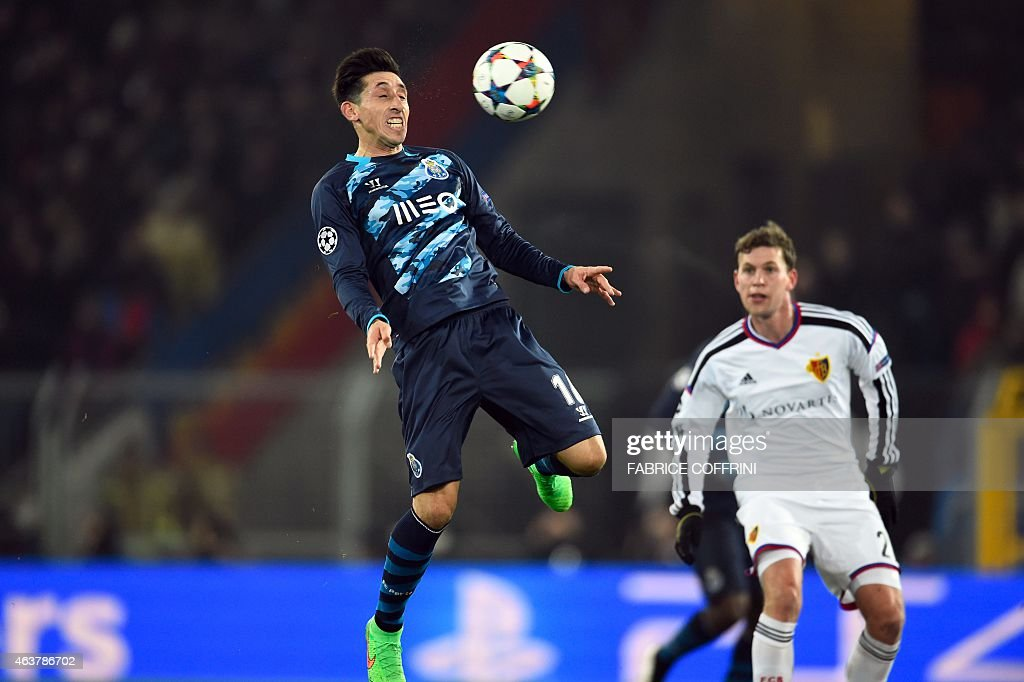 Porto's Mexican midfielder Hector Herrera (L) controls the bqll ahead of Basel's Swiss midfielder Fabian Frei during the UEFA Champions League round of 16 first leg football match between Basel (FCB) and Porto (FCP) on February 18, 2015 at the St. Jakob-Park stadium in Basel.