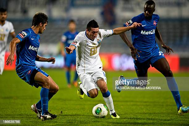 FC Porto's Mexican midfielder Hector Herrera vies with Belenenses' French forward Mamadou Diawara and Belenenses' defender Filipe Ferreira during the...