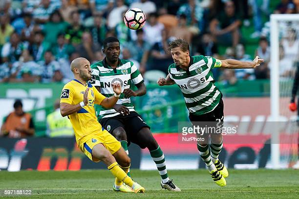 Porto's midfielder Andre Andre vies for the ball with Sporting's midfielder William Carvalho and Sporting's midfielder Adrien Silva during Premier...