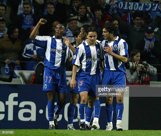 Porto's South African Benni MacCarthy celebrates with teammates Russian Dimitri Alenitchev and Nuno Valente after scoring their first goal during...