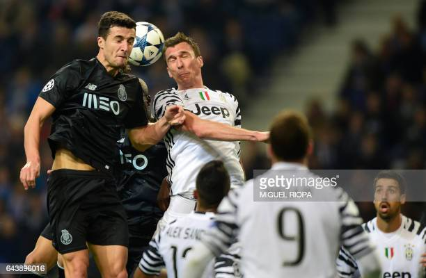 Porto's Spanish defender Ivan Marcano jumps for the ball with Juventus' Croatian forward Mario Mandzuki during the UEFA Champions League round of 16...