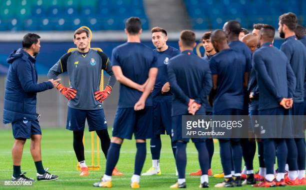 Porto's Spanish goalkeeper Iker Casillas and teammates listen to Portuguese head coach Sergio Conceicao speaking during a training session on the eve...