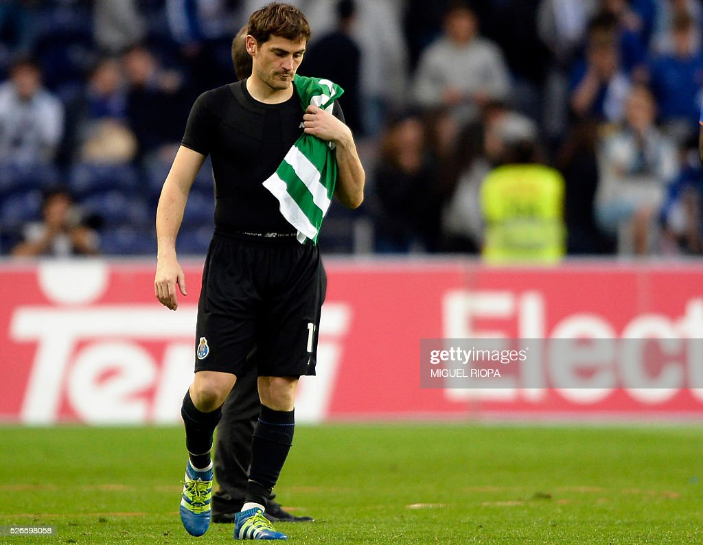 Porto's Spanish goalkeeper Iker Casillas carries a Sporting's jersey as he leaves pitch at the end of the Portuguese league football match FC Porto vs Sporting CP at the Dragao stadium in Porto on April 30, 2016. Sporting won the match 3-1. / AFP / MIGUEL