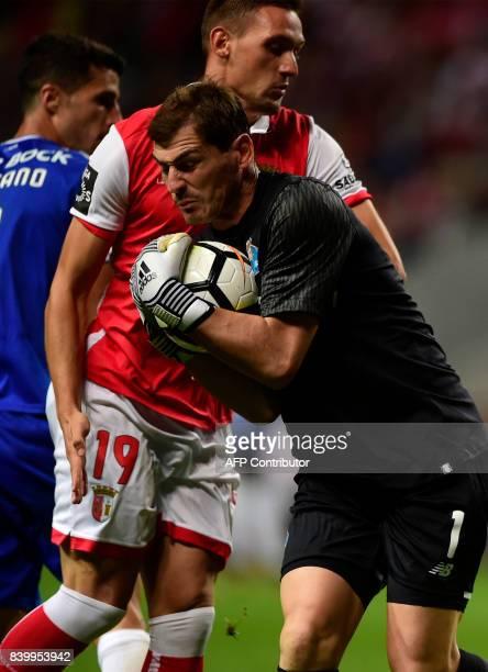 Porto's Spanish goalkeeper Iker Casillas catches the ball next to Sporting Braga's Serbian forward Nikola Stojiljkovic during the Portuguese league...