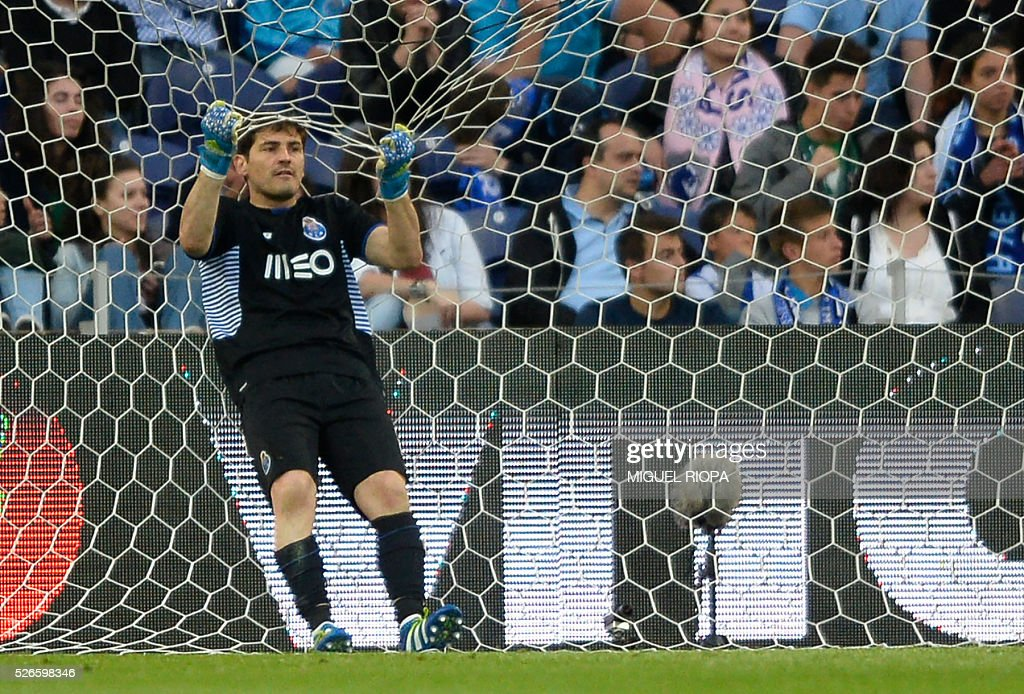 Porto's Spanish goalkeeper Iker Casillas grabs the goal's net after Sporting CP's 3rd goal during the Portuguese league football match FC Porto vs Sporting CP at the Dragao stadium in Porto on April 30, 2016. Sporting won the match 3-1. / AFP / MIGUEL