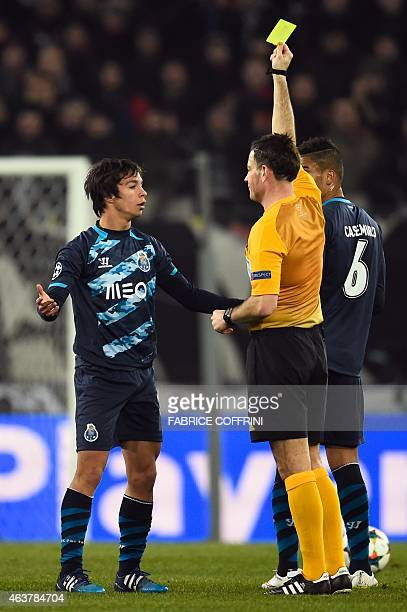 Porto's Spanish midfielder Oliver Torres gets a yellow card from English referee Mark Clattenburg during the UEFA Champions League round of 16 first...