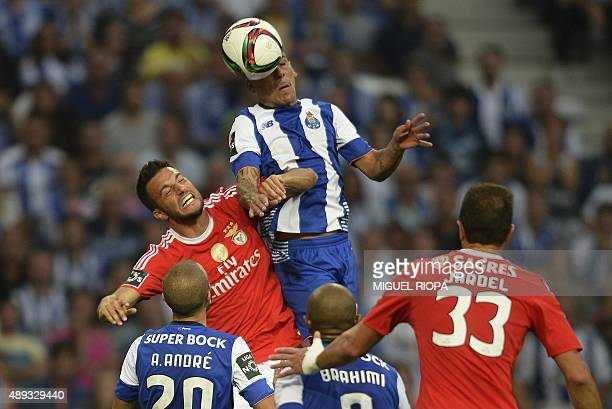 Porto's Uruguayan defender Maxi Pereira heads the ball with Benfica's Greek midfielder Andreas Samaris during the Portuguese league football match FC...