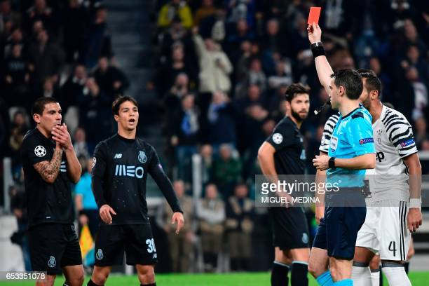 Porto's Uruguayan defender Maxi Pereira receives a red card from referee Ovidiu Hategan during the UEFA Champions League football match Juventus vs...