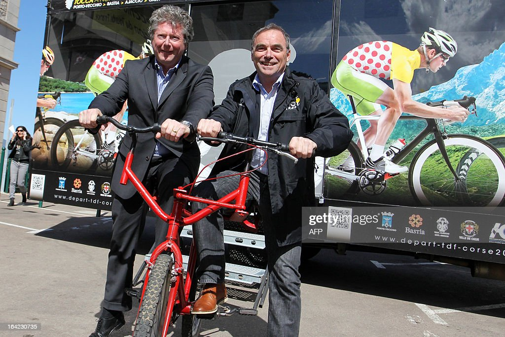Porto-Vecchio Mayor Georges Mela (L) and Bernard Hinault, French former cyclist champion and member of the directory board of the Tour de France cycling race, pose on a bicycle handlebar dual on March 21, 2013 in Porto-Vecchio, on the French Mediterranean island of Corsica, during an event to uncloak the countdown board 100 days ahead of the race which will start from Porto-Vecchio.