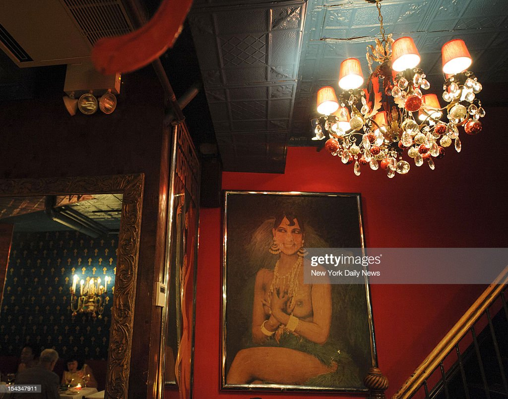 A portrait and chandelier lead upstairs to the exotic bathrooms at Chez Josephine restaurant.