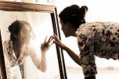 Artist mid adult woman looking herself on mirror. Dusts and dirts on the mirror...